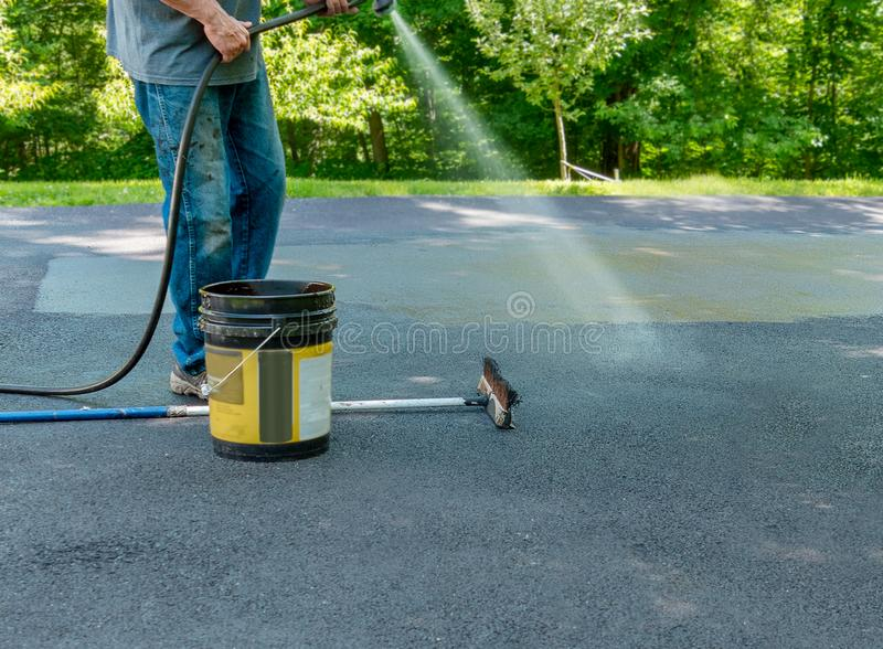 Pouring asphalt sealant on driveway. Do it yourself home maintenance. Driveway resealing repair. Spraying a light mist of water on driveway before applying stock photo