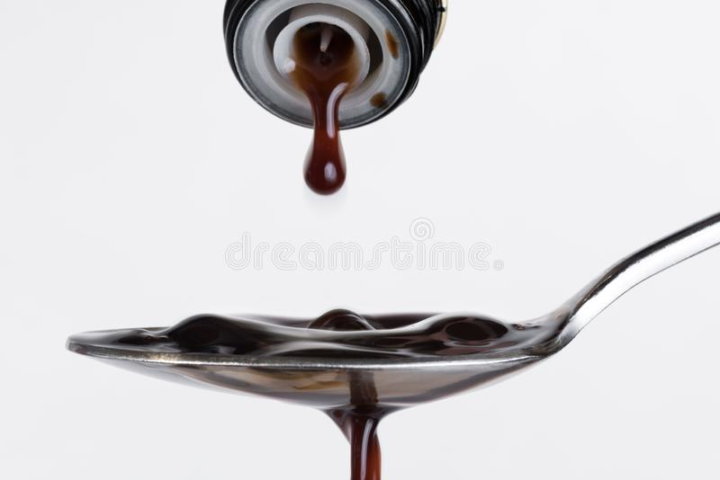 Pouring Balsamic Vinegar onto a Spoon. Pouring balsamic vinegar from a container onto a spoon against white background stock photos