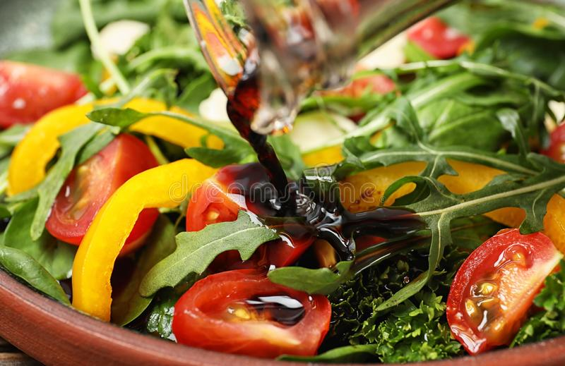 Pouring balsamic vinegar to fresh vegetable salad on plate. Closeup royalty free stock photography