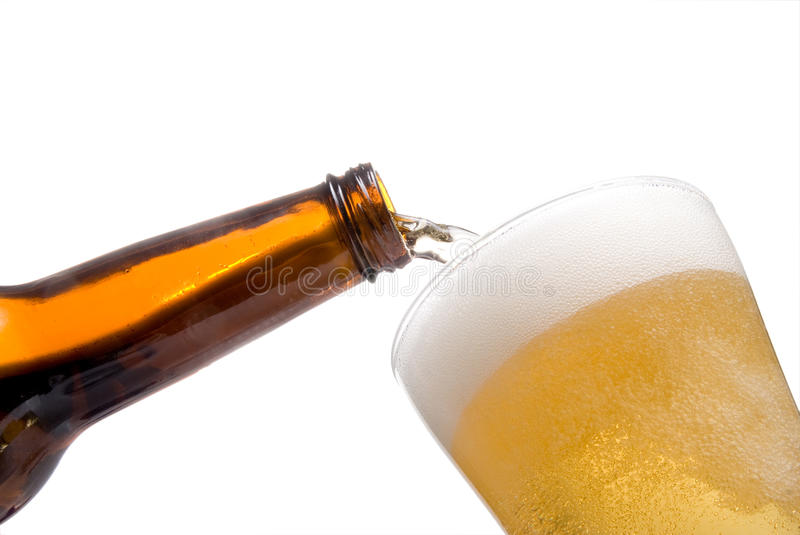 Pouring Beer. A person Pouring Beer into a pilsner glass stock photography