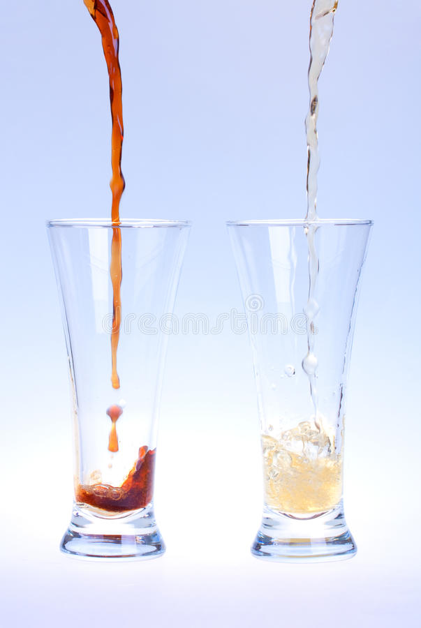 Pouring beer. Glass on blue background stock photography