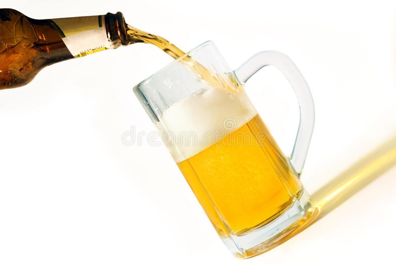 Pouring Beer. Into a mug, isolated on white background stock photography