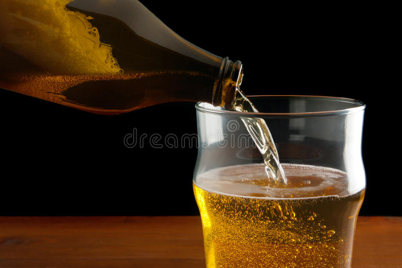 Pouring Beer. Pouring lager beer in a mug stock photos