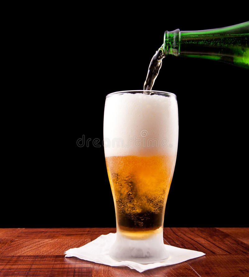 Pouring a beer. Bottle pouring a beer into a chilled glass on a black background stock photos
