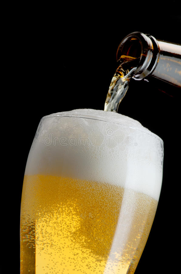 Pouring beer. Into a glass, motion shot royalty free stock photography
