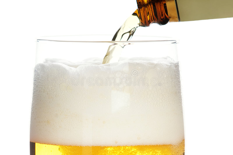 Pouring beer. Pouring fresh beer in to glass, isolated on white stock photography