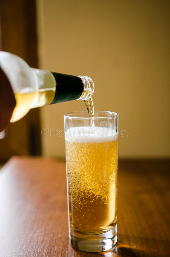 Pouring beer. From a bottle in a glass, natural light royalty free stock image