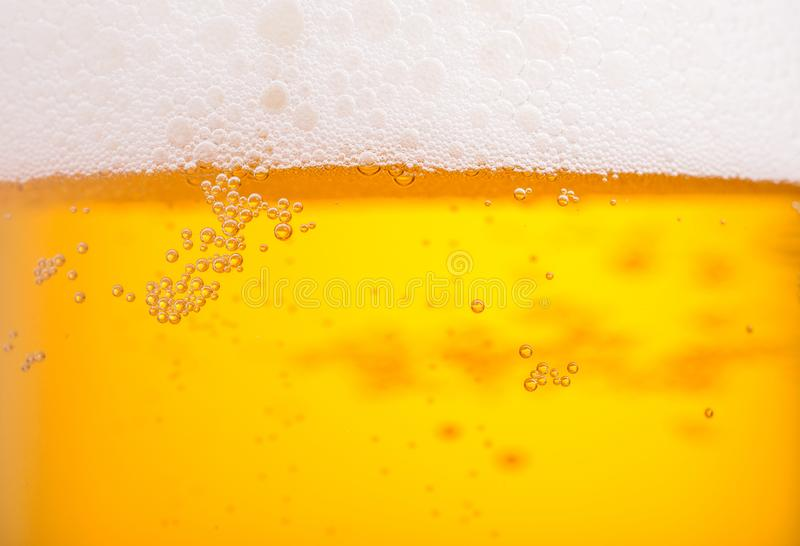 Pouring beer with bubble froth in glass for background stock photo