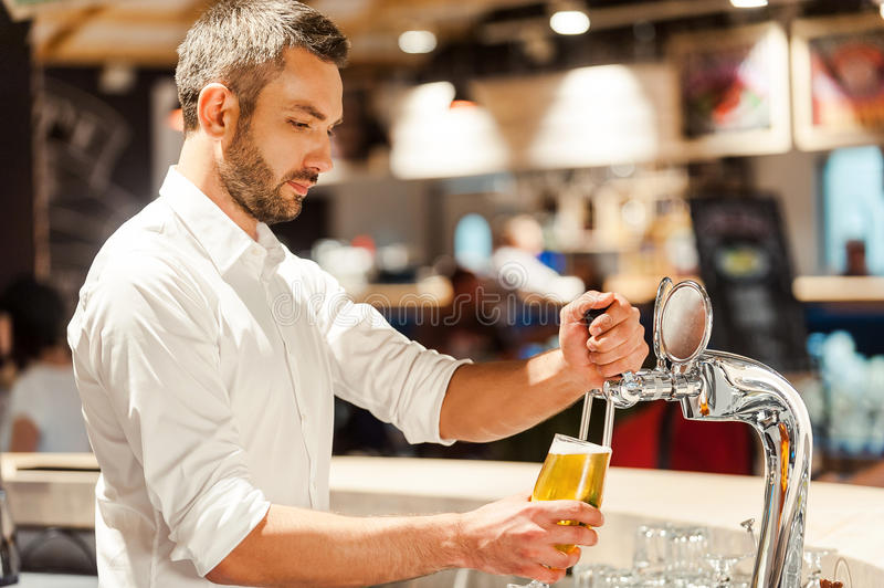 Pouring beer for client. Side view of young bartender pouring beer while standing at the bar counter stock photos