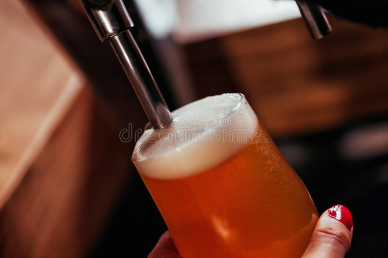 Pouring Beer. Close Up Of Waitress Hands Pouring Beer Into Glass royalty free stock image