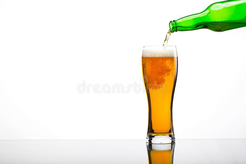 Pouring beer in glass. Ower white stock photos