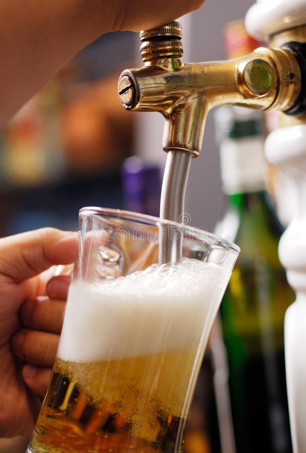 Pouring beer into glass. Pouring beer into the glass stock photo