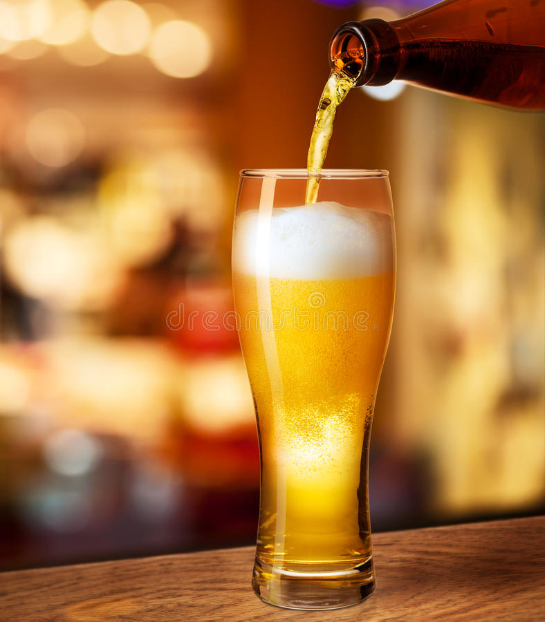 Pouring beer in glass on bar desk. Pouring beer in glass on bar or pub desk royalty free stock images