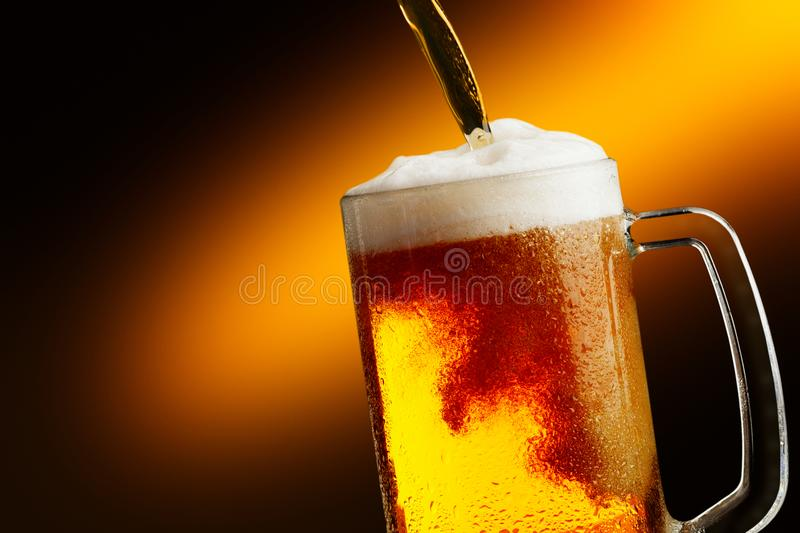 Pouring beer into glass. With foam stock photography