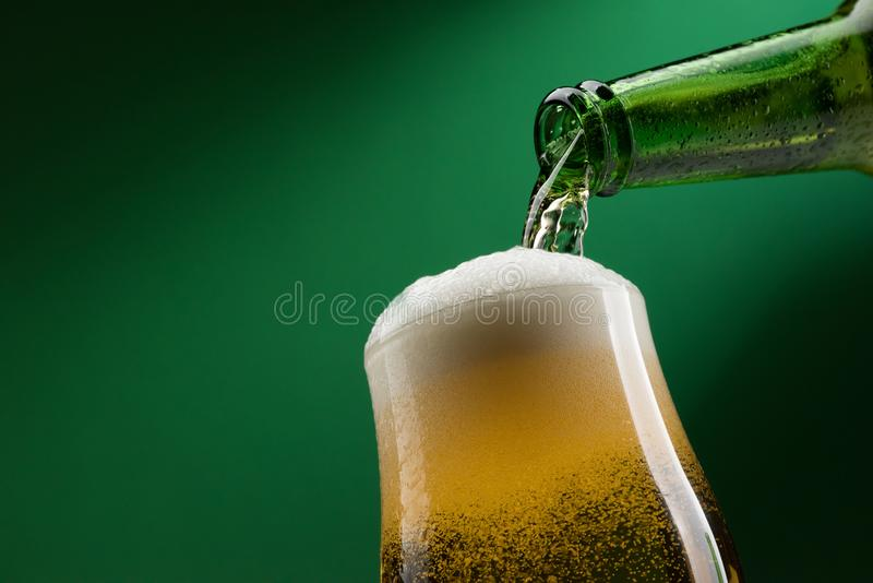 Pouring beer into a glass. Pouring fresh beer from a bottle into a glass, alcoholic drinks and celebration concept royalty free stock photography