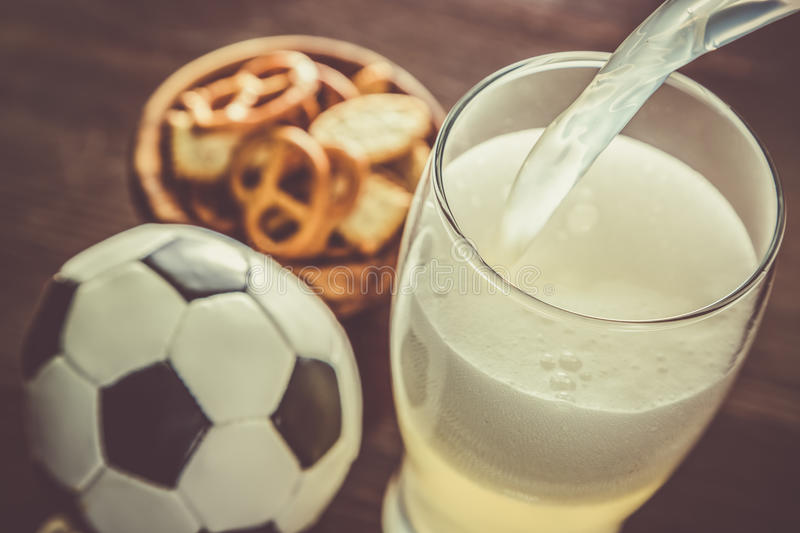 Pouring beer into glass with snacks and football. Toned stock image