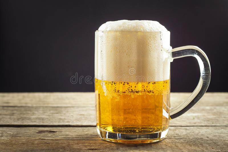 Pouring beer into a glass on a wooden table. Alcoholic beverages. Alcohol-free beer. Sale of beer to the bar. Pouring beer into a glass on a wooden table stock photos