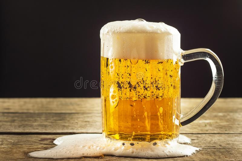 Pouring beer into a glass on a wooden table. Alcoholic beverages. Alcohol-free beer. Sale of beer to the bar. Pouring beer into a glass on a wooden table royalty free stock photos