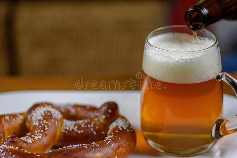 pouring beer into a large glass mug on plate with warm soft pretzel appetizer royalty free stock images