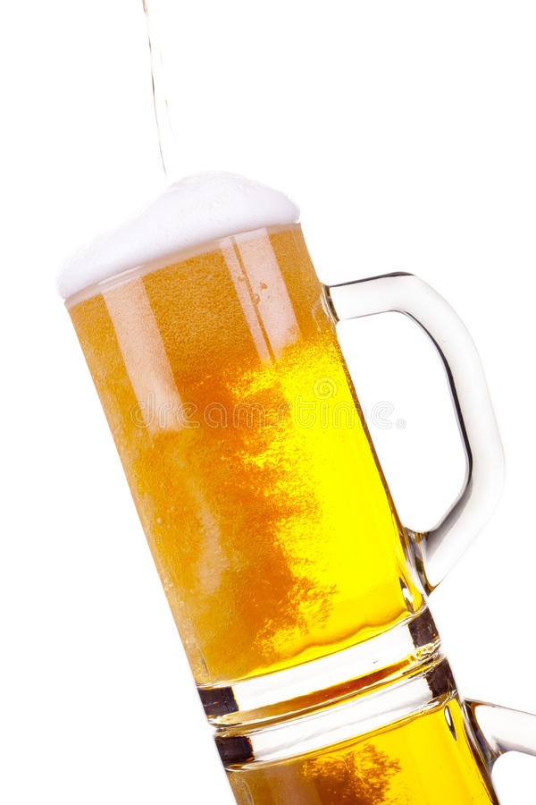 Pouring beer into mug. Over a white background royalty free stock photos
