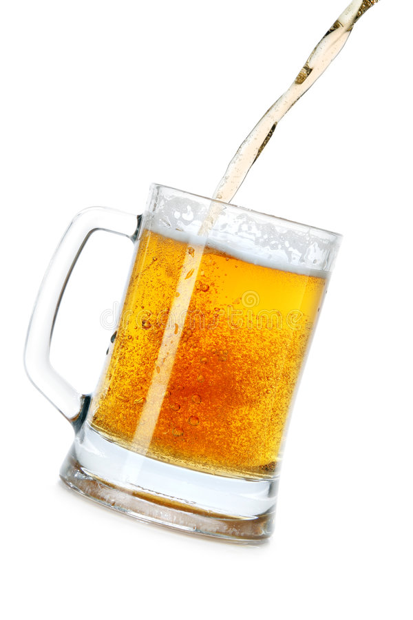 Pouring beer into mug. Isolated over a white background royalty free stock image