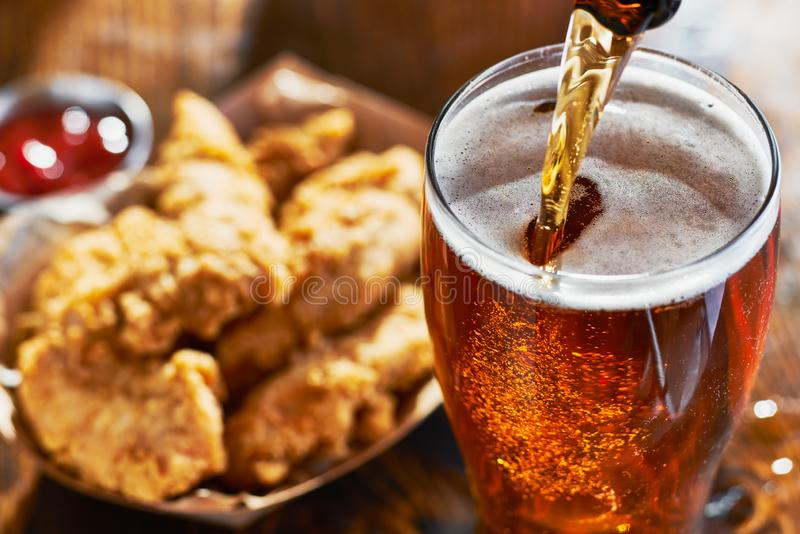 Pouring beer into mug with fried chicken tenders in background. With focus on beer stock photos