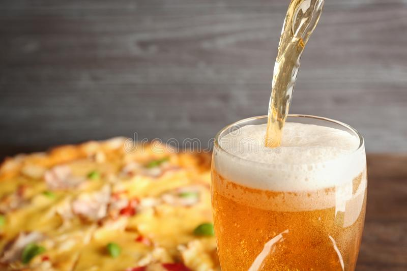 Pouring beer on pizza background. Closeup stock image