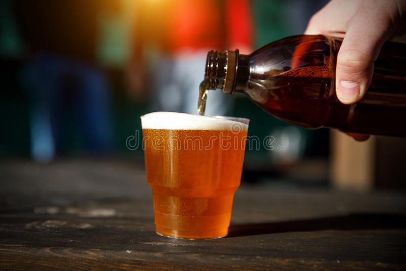 Pouring beer into a plastic small glass from a plastic bottle royalty free stock image