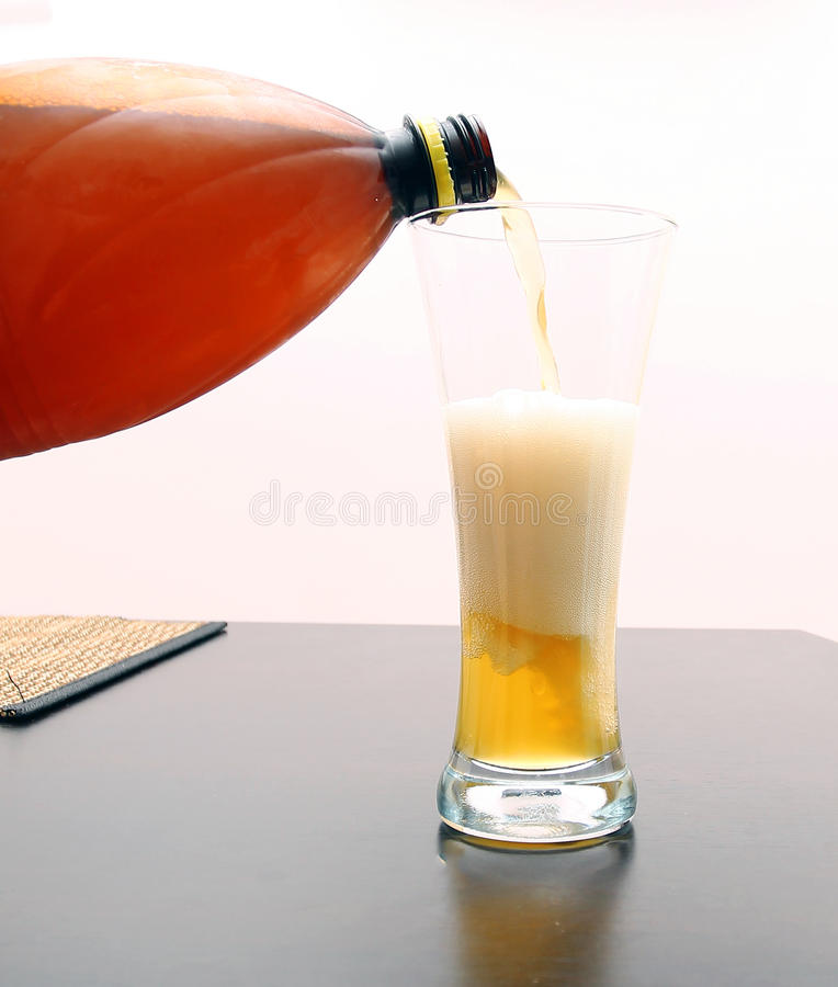 Pouring beer. Pouring white beer from plastic bottle to a clean beer glass royalty free stock images