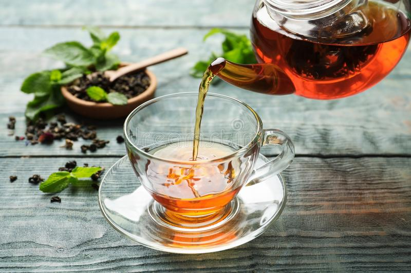 Pouring black tea into glass cup. On wooden table stock photos