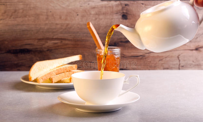 Pouring black tea. In to white cup royalty free stock photos