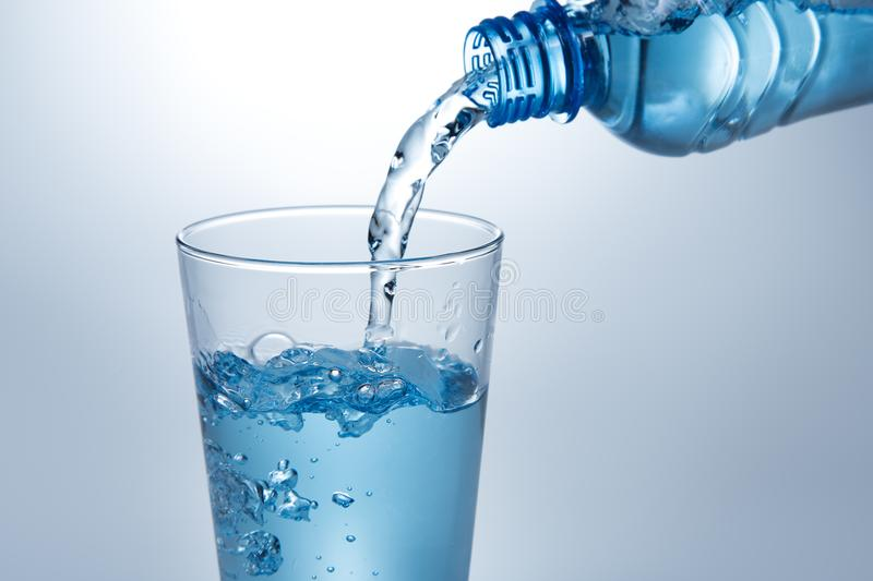 Pouring water from bottle into glass. Pouring blue water from bottle into glass stock photo