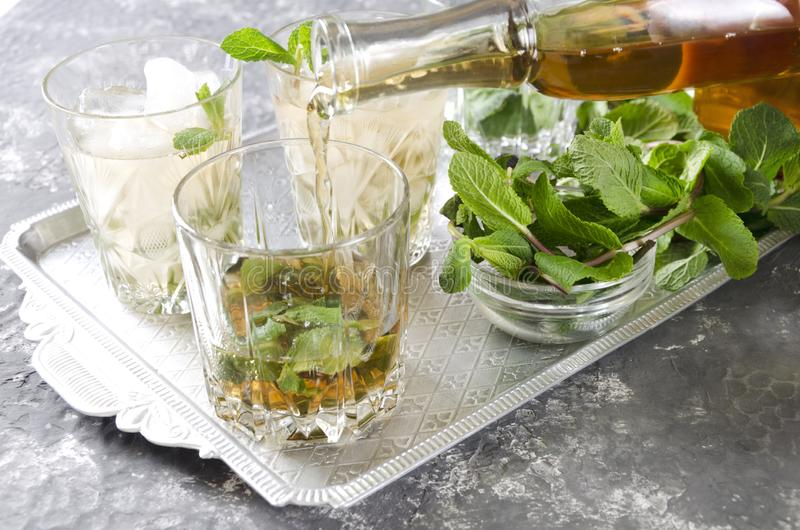 Pouring bourbon into a glass, process of making mint julep.Closeup of an old-fashioned glass with mint and crushed ice on the silv. Glasses of mint julep.Table royalty free stock photo
