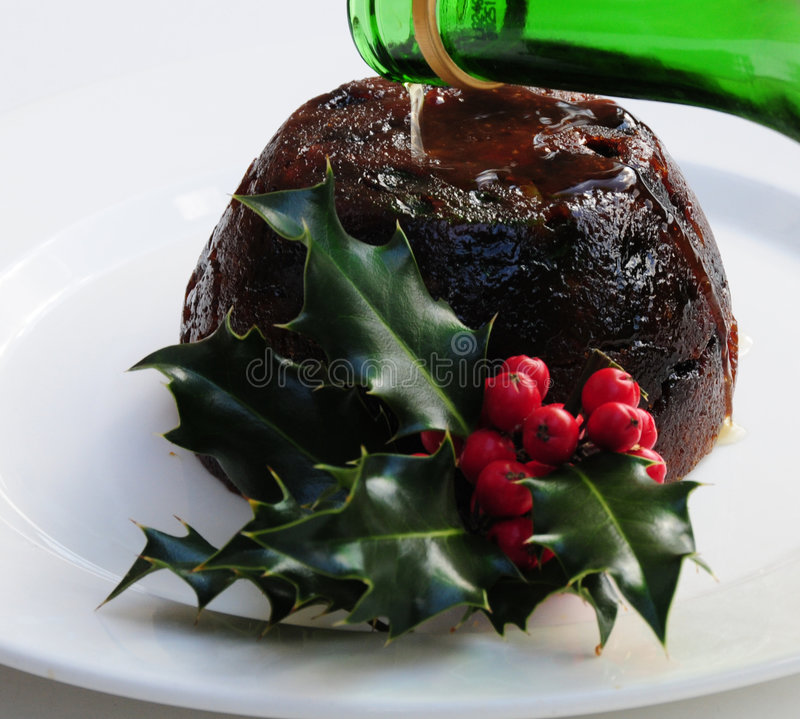 Pouring brandy onto christmas pudding royalty free stock images