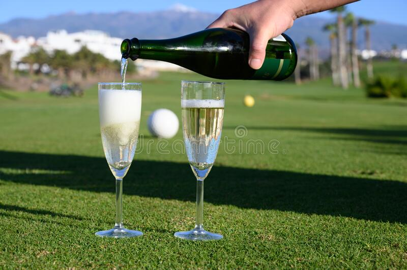 Pouring of bubbles white champagne or cava wine during golf competition event or celebration on green golf club grass with. Mountains view in sunny day royalty free stock images