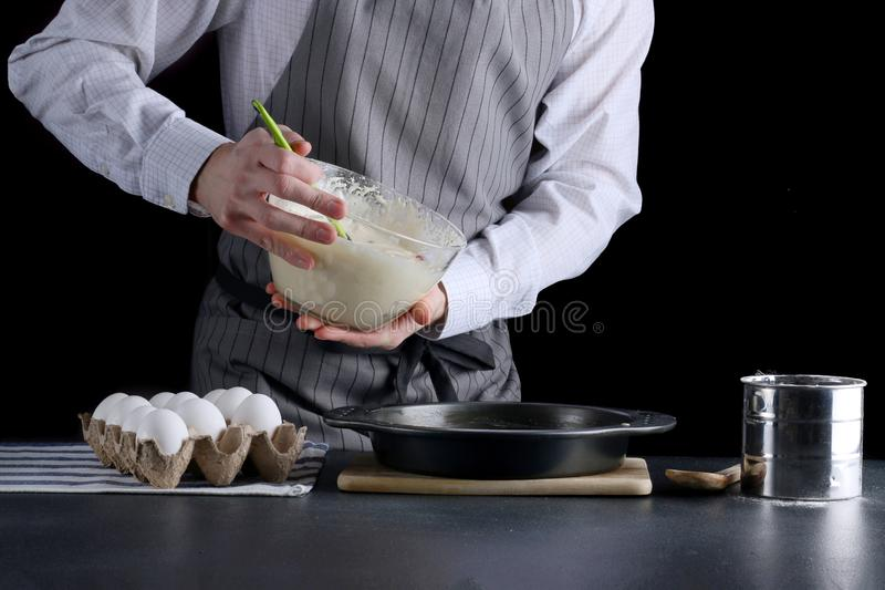 Pouring cake dough into baking tin. man hold bowl and pouring batter royalty free stock image