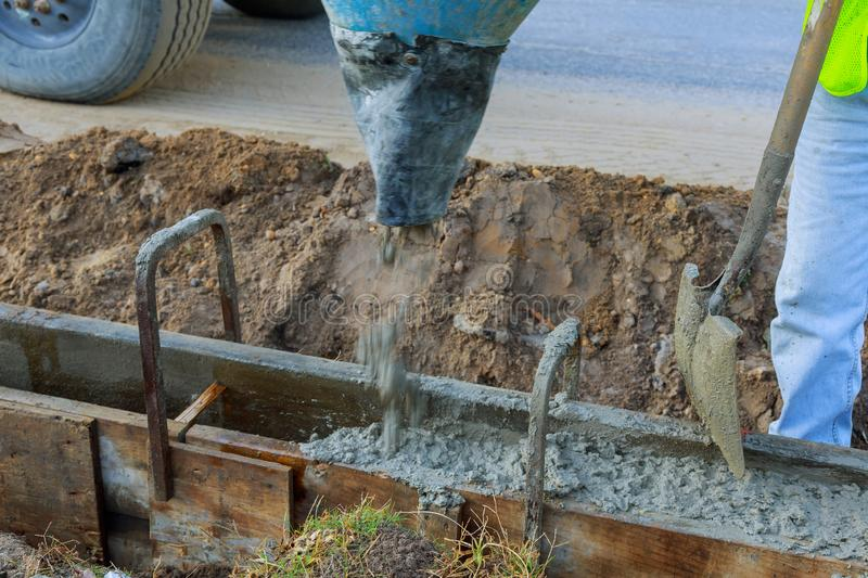 Pouring cement during upgrade to residential street. Masonry construction workers pouring cement during to residential street upgrade stock photography