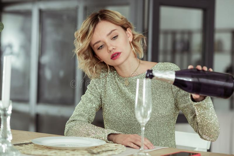 Blonde-haired curly woman pouring champagne into glass stock images