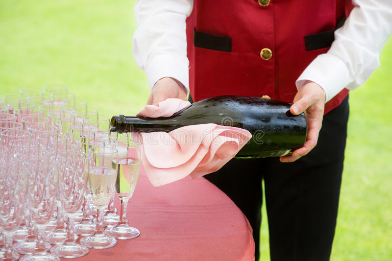 Pouring champagne. Waiter pouring champagne on a party stock image