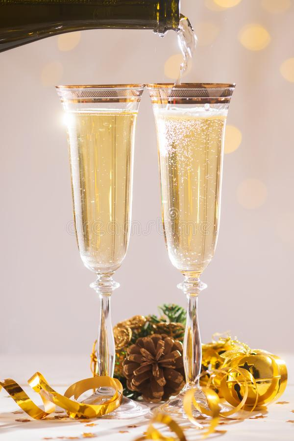 Pouring champagne wine into glasses over blur spots light background ready to bring in the New Year royalty free stock photo