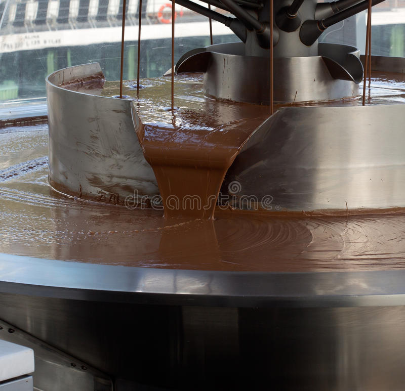 Pouring chocolate in a chocolate factory. The Pouring chocolate in a chocolate factory royalty free stock image