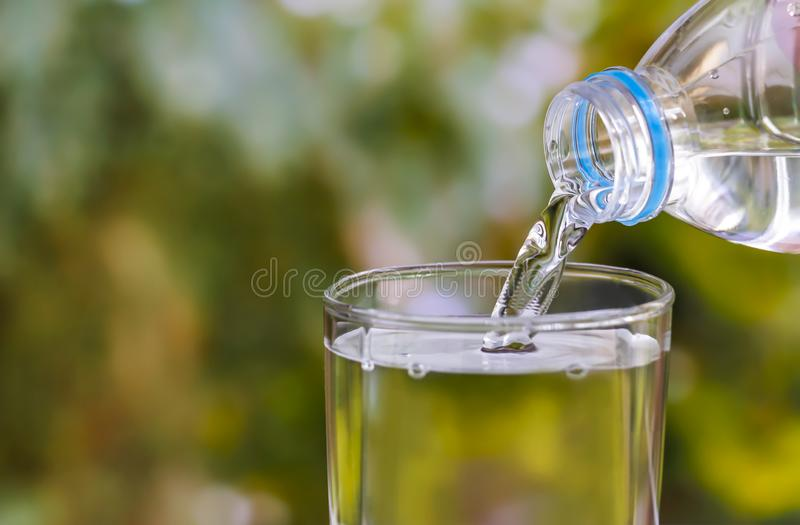 Pouring of clear drink water from bottle into the glass on blurred green nature background with copy space for text. stock image