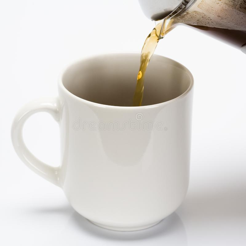 Pouring coffe into cup royalty free stock image