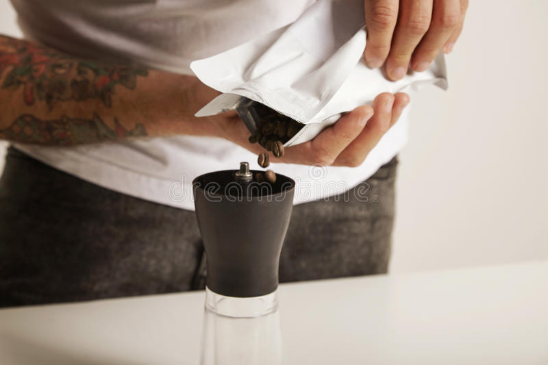 Pouring coffee beans into grinder stock images