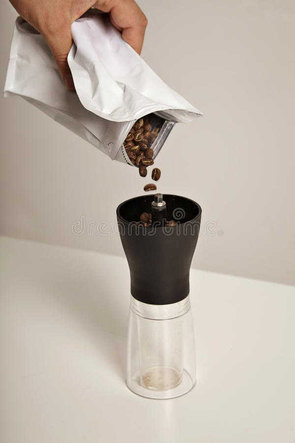 Pouring coffee beans into grinder royalty free stock photos