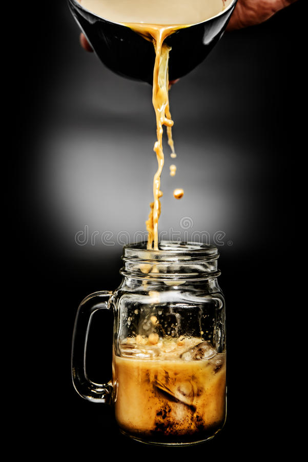 Pouring Coffee into Clear Glass with Ice stock photography