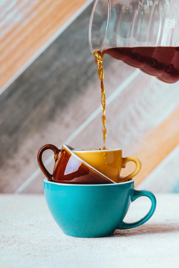 Pouring coffee on a cup on colorfull background. Woman hand Pouring coffee on a cup on colorfull background royalty free stock images