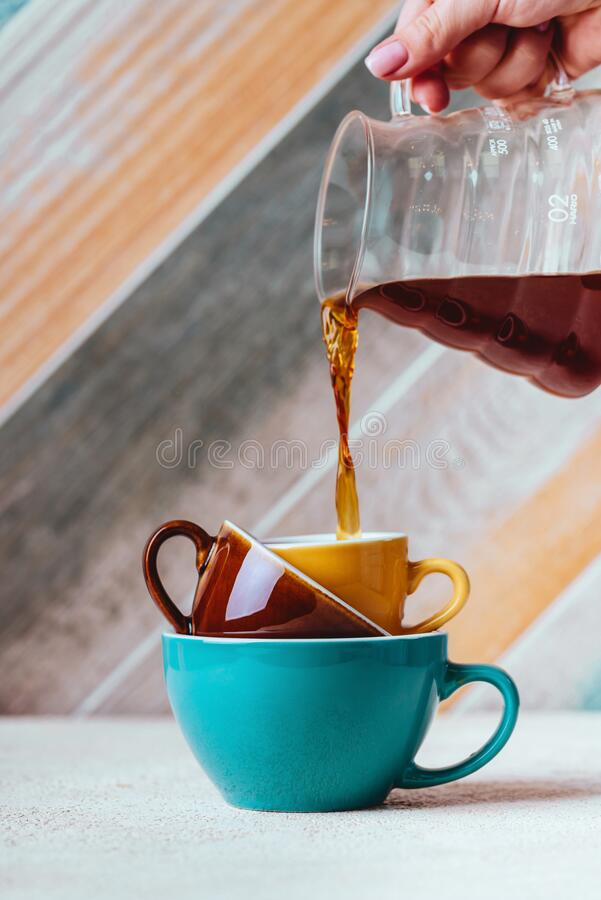 Pouring coffee on a cup on colorfull background. Woman hand Pouring coffee on a cup on colorfull background royalty free stock photography
