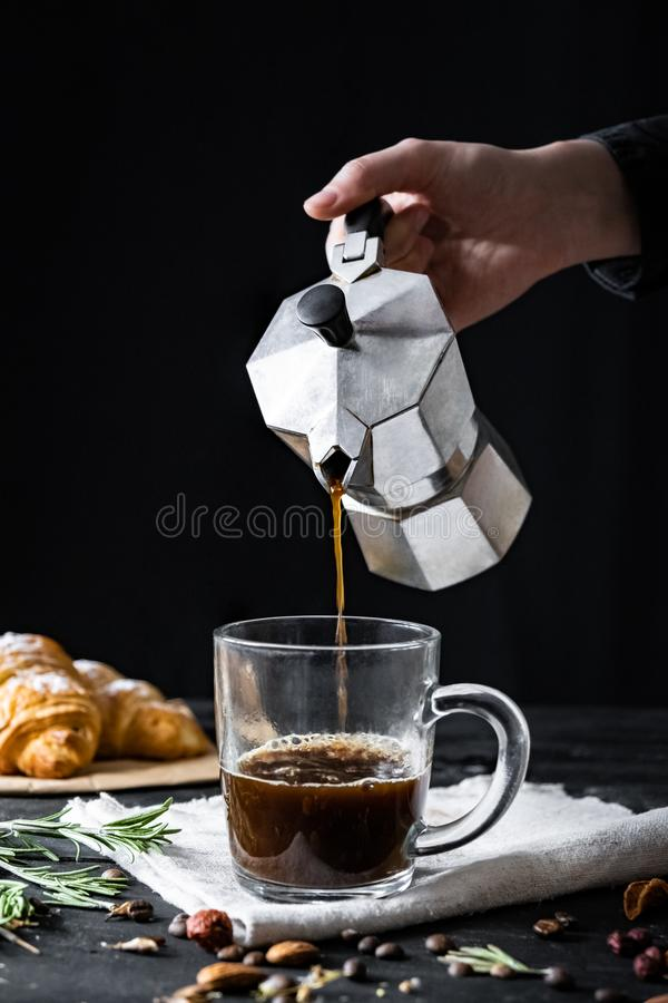 Pouring coffee from an italian percolator, shot in low key stock photos