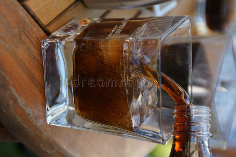 Pouring cola in the glass stock image